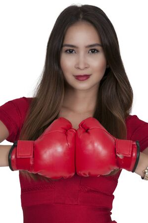 tough girl: Beautiful young woman in a red dress wearing a pair of boxing gloves
