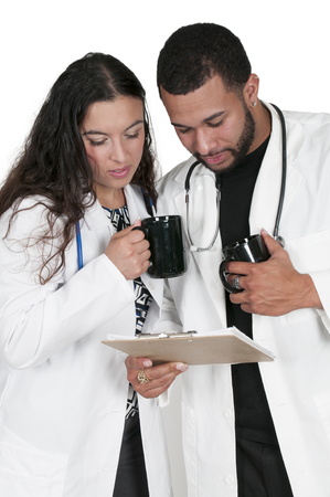 lab coats: Beautiful young woman and man doctors in a lab coats holding a patient record Stock Photo