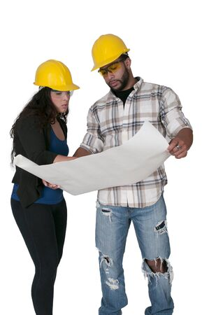 ppe: Construction Worker on a job site inspecting blueprints Stock Photo