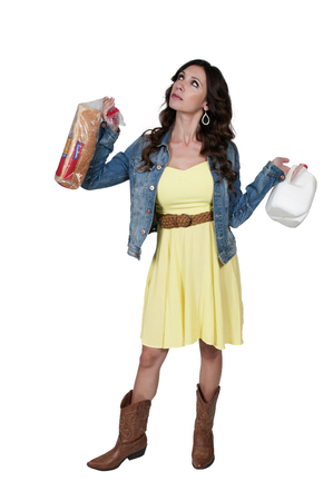 inclement: Woman holding bread and milk getting ready for snow Stock Photo