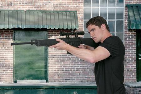 assault: Handsome man holding an automatic assault rifle