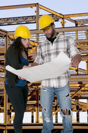 site: Construction Worker on a job site inspecting blueprints Stock Photo