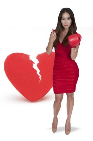 Beautiful woman in wearing a boxing glove in front of a broken heart - heartbreaker Stock Photo