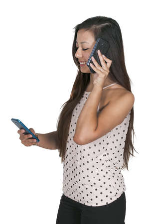 Beautiful woman talking and multitasking while juggling multiple cell phones and conversations Stock Photo