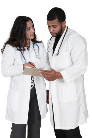 lab coats: Young doctors in lab coats discussing a patient record Stock Photo