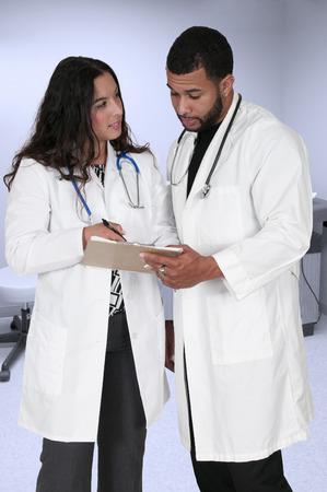 laboratorio clinico: J�venes m�dicos en batas de laboratorio en discusiones sobre un registro de paciente Foto de archivo