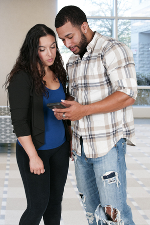 accessing: Woman and man texting or accessing the Internet with a cell phone Stock Photo