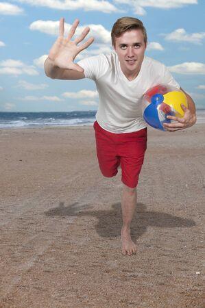beachball: Young man holding a beach ball at the ocean Stock Photo