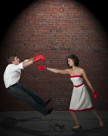 Young couple having a fight with boxing gloves