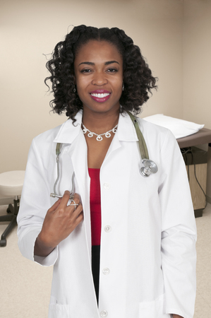 labcoat: Beautiful young female doctor on her rounds Stock Photo