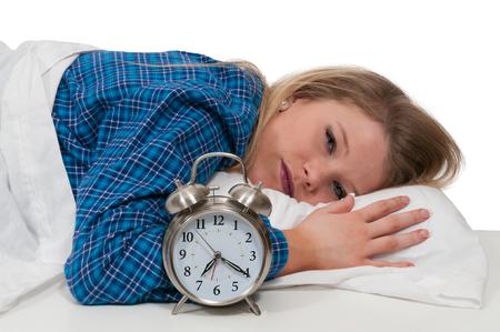 Beautiful young sleeping woman waking up with an alarm clock