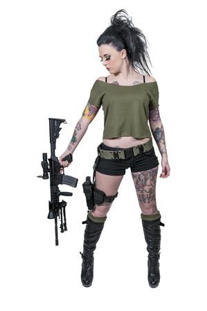 assault rifle: Beautiful young tattooed woman holding an automatic assault rifle and pistol Stock Photo