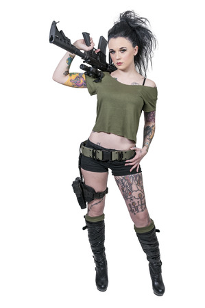 Beautiful young tattooed woman holding an automatic assault rifle photo