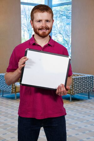 blank sign: Young man holding up a blank sign Stock Photo