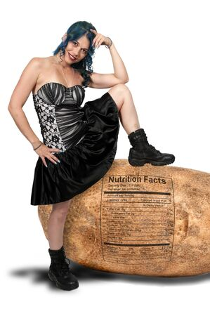 Beautiful young sexy woman with her foot up on a giant potato Stock Photo