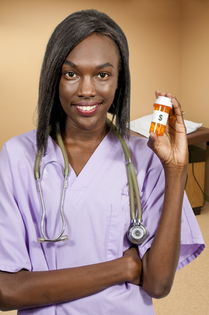 labcoat: Beautiful young female doctor on her rounds holding a pill bottle of prescription medication