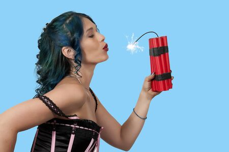 Sexy young woman holding sticks of dynamite Stock Photo