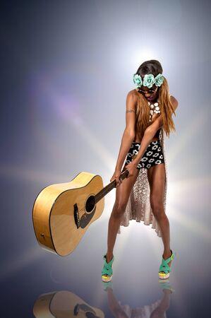 smashing: Female rock star guitarist smashing a guitar