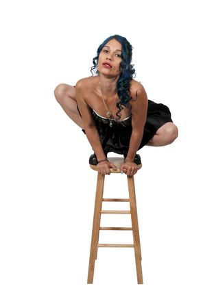 Beautiful acrobatic woman balancing on a stool