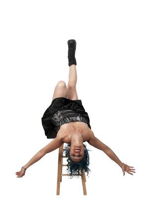 cabeza abajo: Hermosa mujer de equilibrio en posición invertida sobre un taburete Foto de archivo