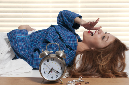 Beautiful young yawning woman waking up with an alarm clock