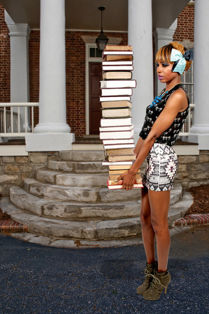 Beautiful woman holding a stack of library books Stock Photo