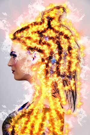 Beautiful young woman or girl with colorful tattoos on fire photo