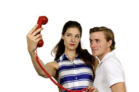 rotary phone: Woman and man trying to take a selfie with a rotary phone