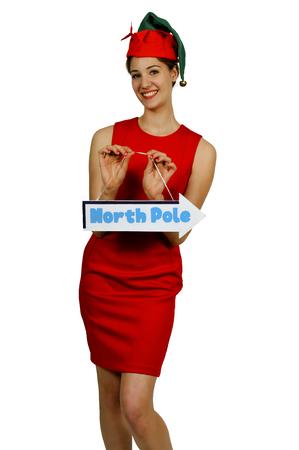 north pole: Beautiful woman Santa elf holding a north pole sign