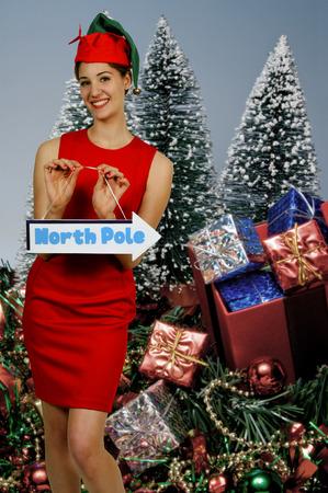 Beautiful woman Santa elf holding a north pole sign