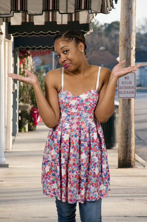 insensitive: Beautiful woman shrugging her shoulders in confusion Stock Photo