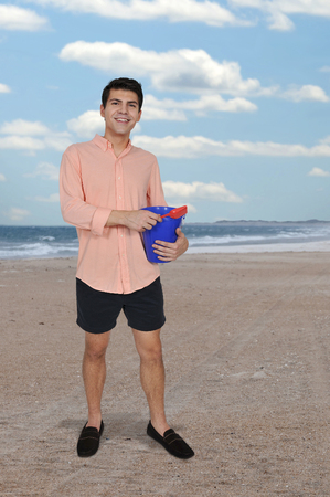 Handsome young man holding a sand pail and a toy shovel Imagens