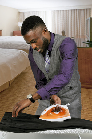 flatiron: Handsome african american man with a clothes iron about to press his clothing Stock Photo