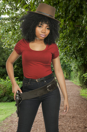 shooters: Beautiful young country girl African American black woman wearing a cowboy hat and revolver
