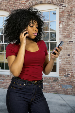 Beautiful woman talking texting and multitasking while juggling multiple cell phones and conversations Stock Photo - 70000083