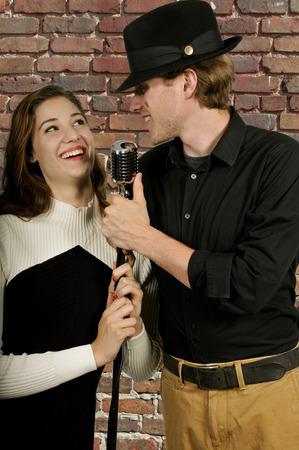Man and woman singing with an old vintage microphone photo