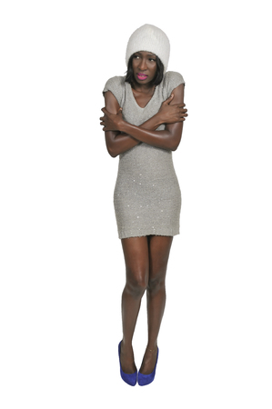 Shivering African American black woman in a short dress trying to keep warm Фото со стока