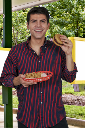 Young man eating a juicy delicious hamburger