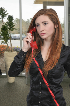 corded: Beautiful young woman talking on a phone Stock Photo