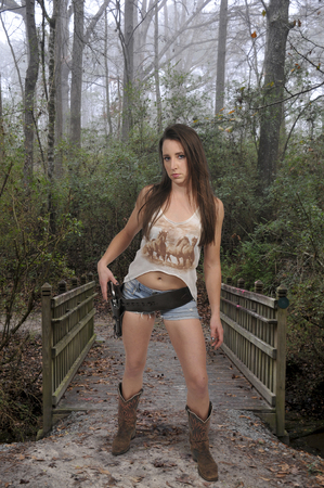 Beautiful young country girl woman cowgirl with a six shooter pistol