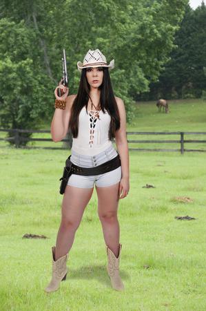 Schöne junge Land Mädchen Frau trägt einen stilvollen Cowboy Hut und Revolver Standard-Bild - 77213775