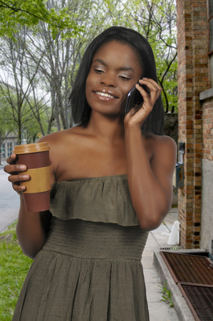 Black African American woman using a cell phone will holding coffee Stok Fotoğraf