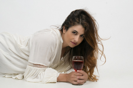 Beautiful woman holding a glass of red chardonnay wine