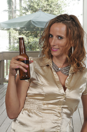 Beautiful young woman drinking a delicious bottle of beer