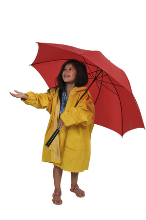 Little girl in a raincoat holding a colorful and fashionable umbrella