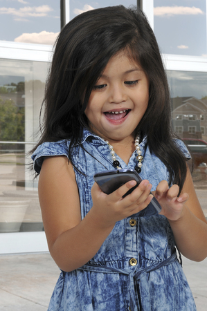 sms: Beautiful little girl texting on a cell phone