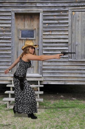 Schöne junge Land Mädchen Frau trägt einen stilvollen Cowboy Hut und Revolver Standard-Bild - 86250717