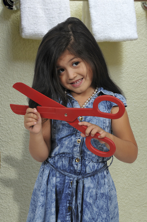 Little girl with big scissors cutting her hair