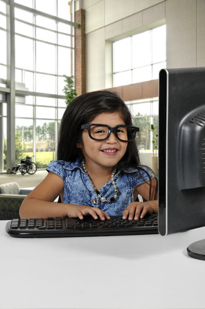 Computer savvy little girl using a desktop computer