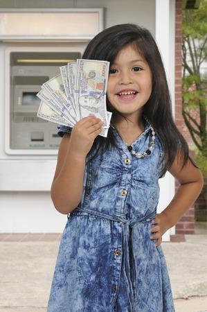 public welfare: Little girl holding a handfull of cash money Stock Photo